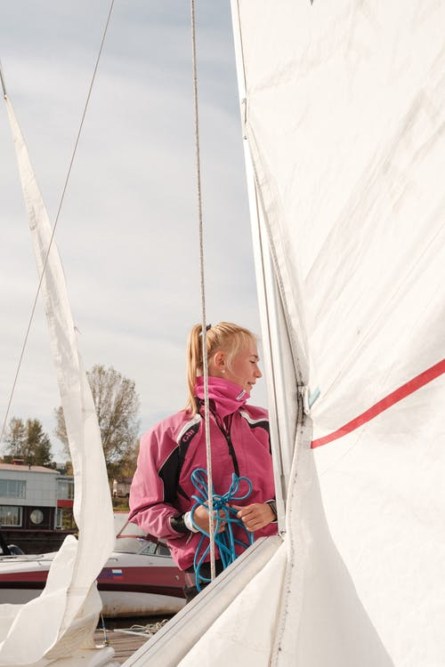 Young woman standing near yacht before sailing