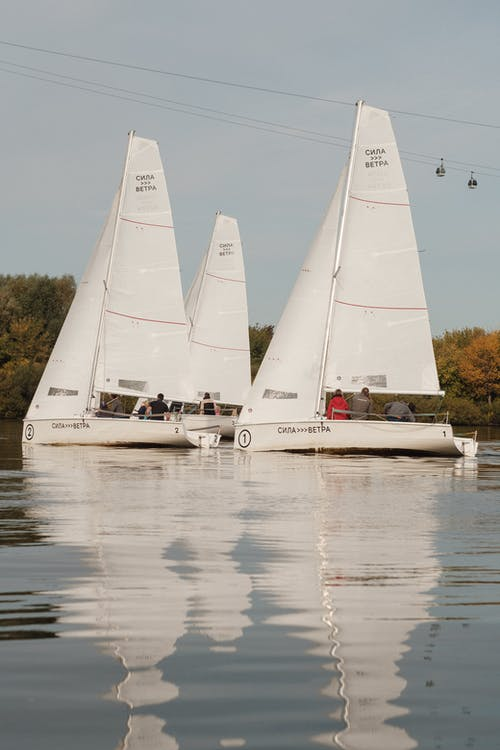 Unrecognizable people in white sailboats floating on lake water surrounded by lush autumn trees during yachting