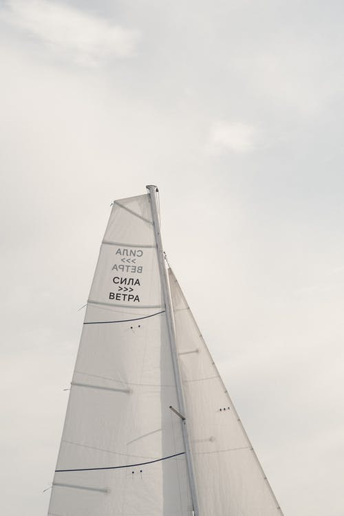 Low angle inscription on tall white sail of boat floating against cloudy sky