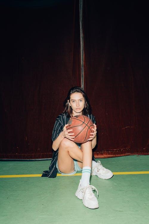Woman Sitting Holding a Basketball