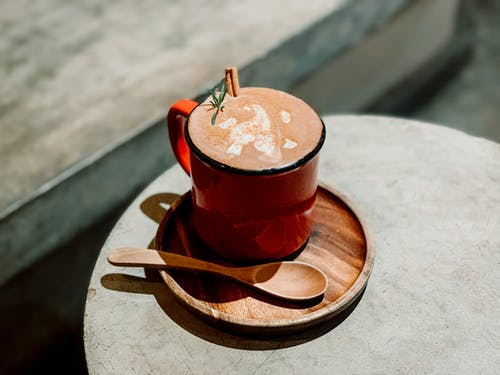 From above of delicious coffee with cinnamon and rosemary on wooden plate with spoon placed on wooden table in sunlight