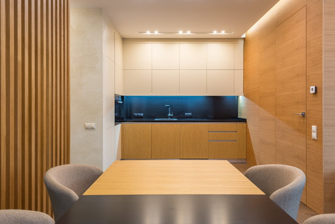 Spacious kitchen with illuminated cooking zone near wooden cabinets and soft chairs around table