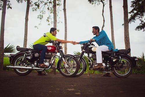 Man in Blue Shirt Riding Motorcycle