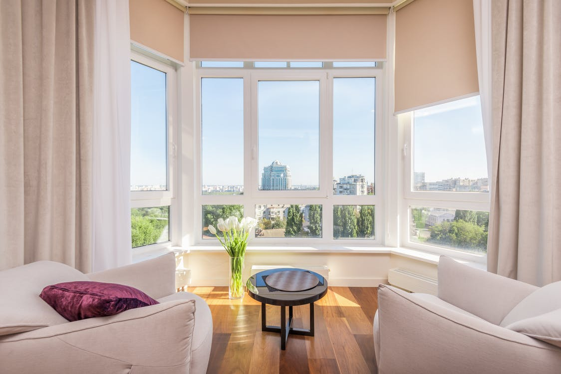 Interior of modern penthouse with comfortable white armchairs and round side table placed near windows overlooking city in sunny day