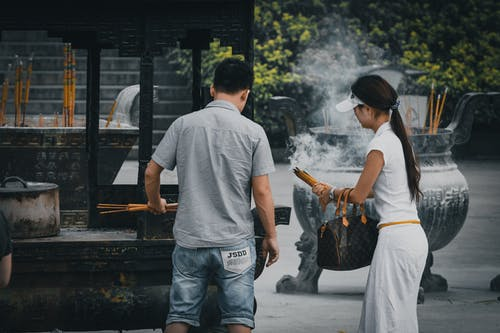 Unrecognizable Asian woman and man near incense burner outdoors