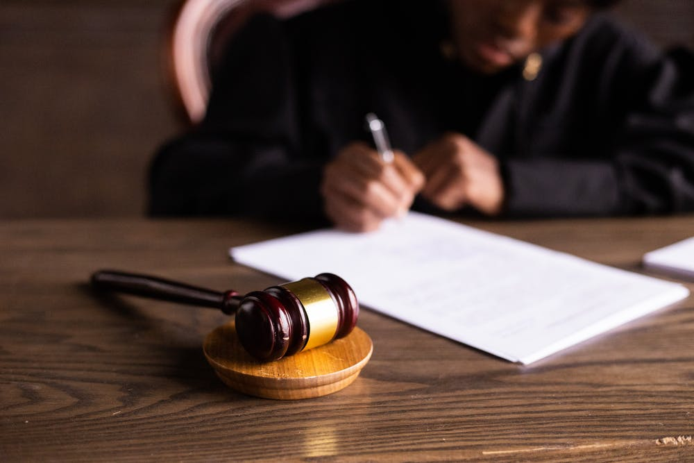 A judge writing on white paper. | Photo: Pexels