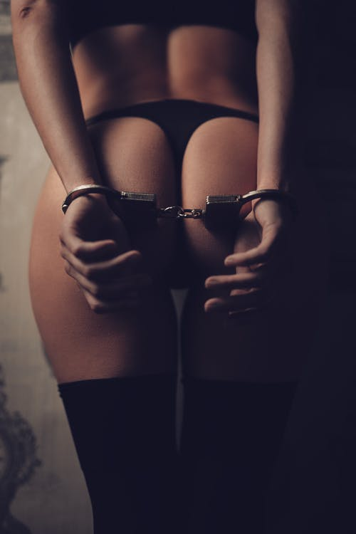 Crop faceless sexy woman in lingerie and handcuffs behind back