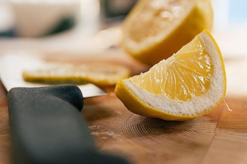 Close-Up Shot of Sliced Lemons beside a Knife on a Wooden Surface