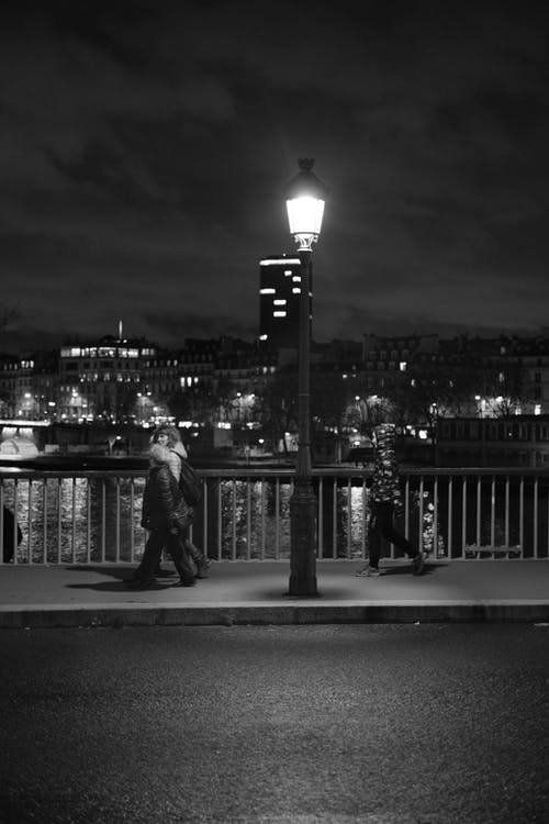People walking on bridge in city in evening
