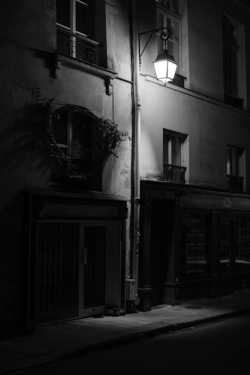 Black and white of empty street with residential building illuminated by street lamp placed in city in evening