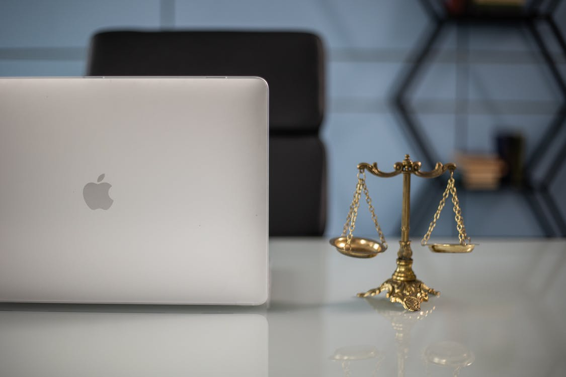 Close-Up Shot of a Laptop beside a Scales of Justice