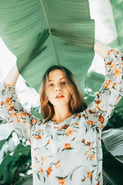 Low-Angle Shot of a Pretty Woman in Floral Top Holding a Green Leaf