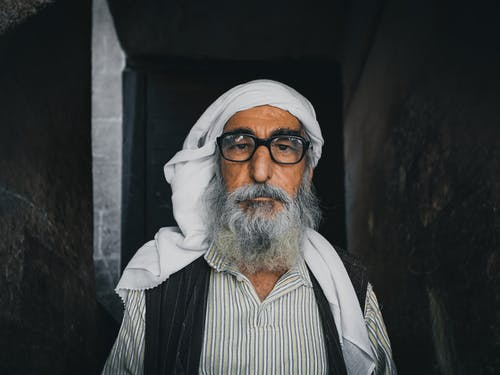 Senior ethnic male with gray beard in traditional apparel and headwear looking at camera between masonry construction walls