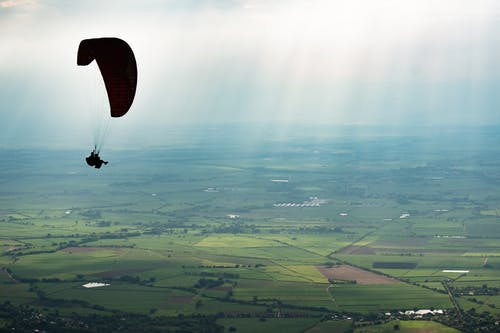 Person Riding Parachute over Green Field