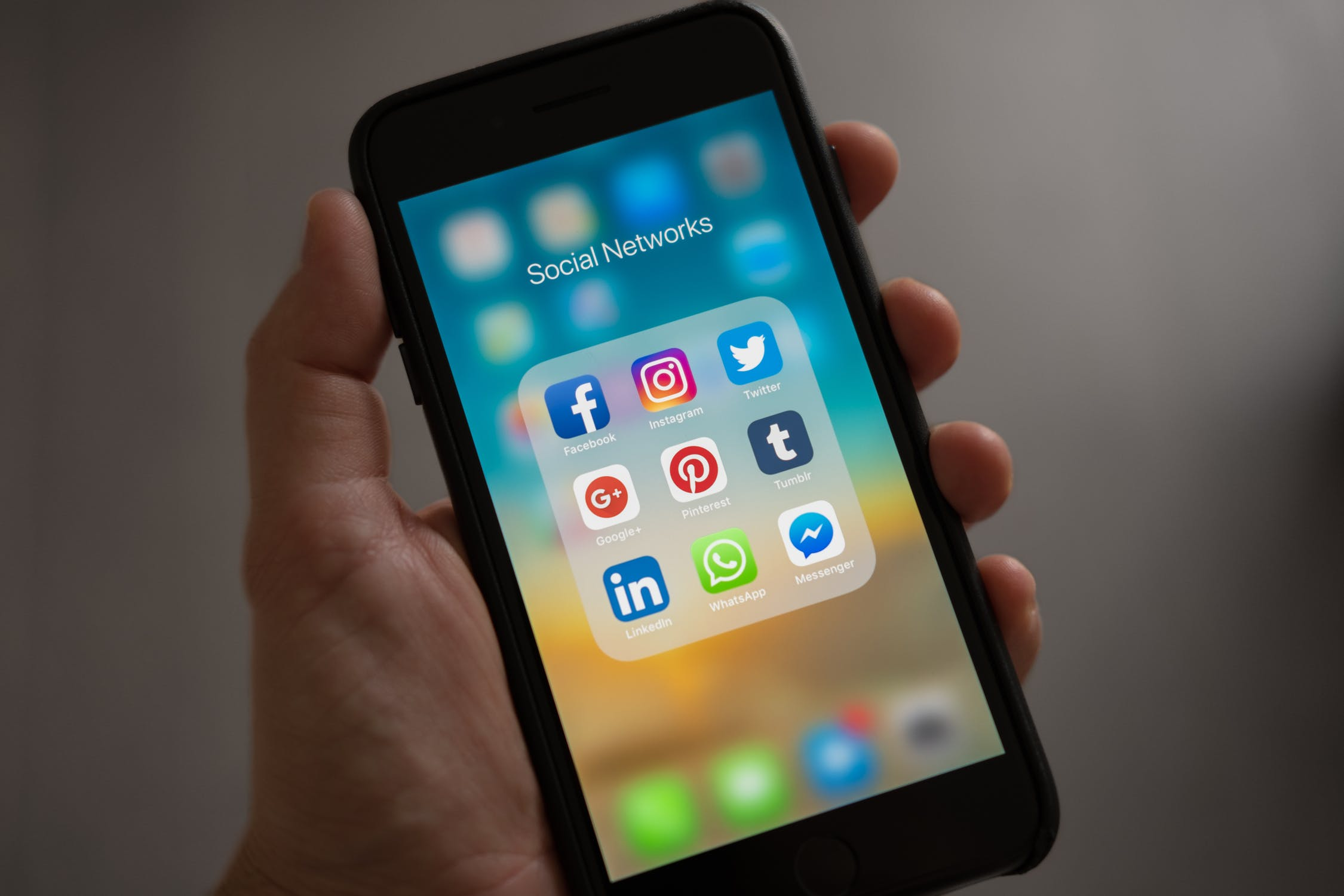 A hand holding a cell phone with the Social Media folder open displaying Facebook, Instagram and Twitter applications. Photo by Tracy LeBlanc. Photo courtesy of Pexels.com