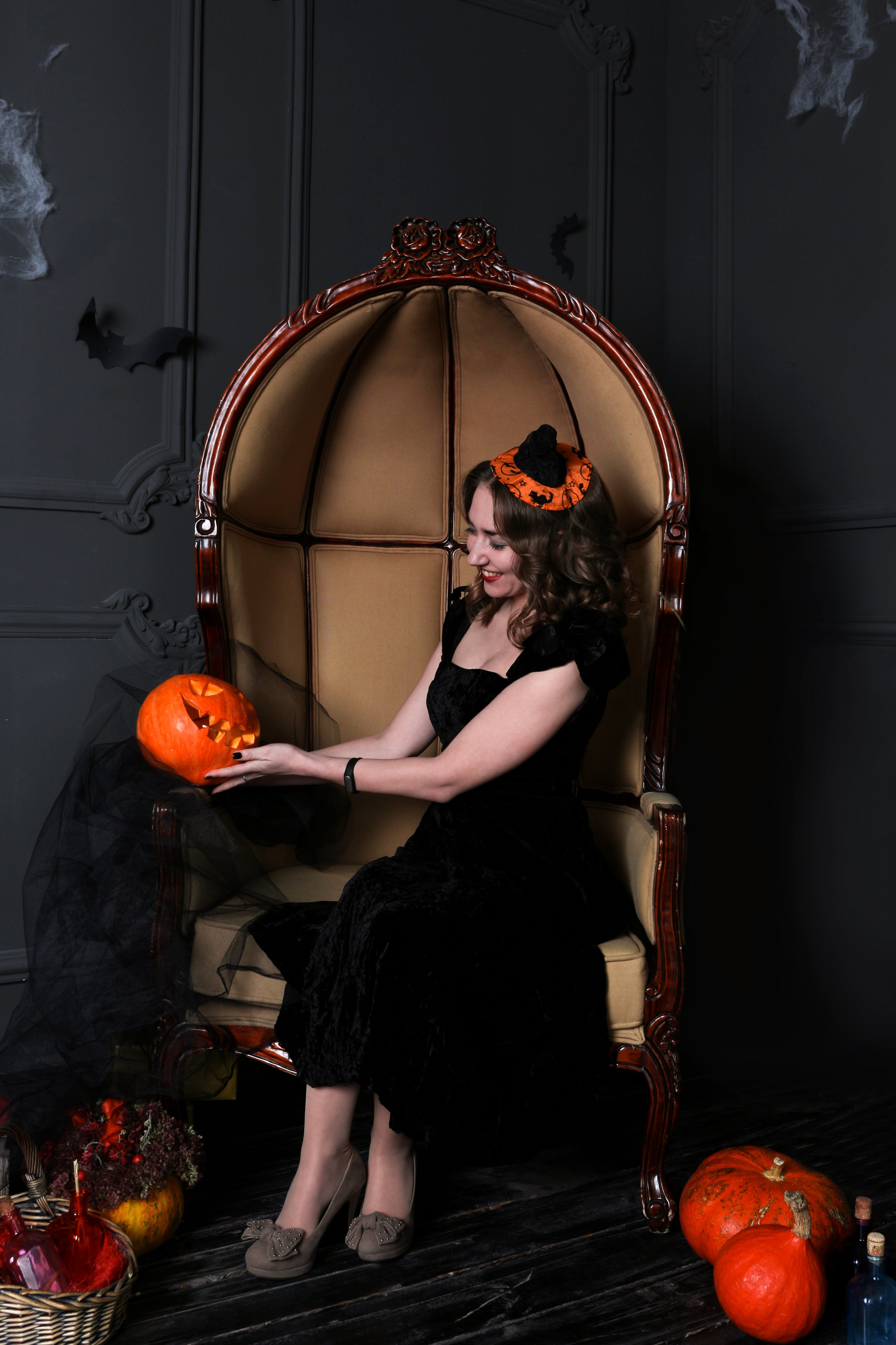 Woman Sitting on Chair Holding Jack-o-lantern