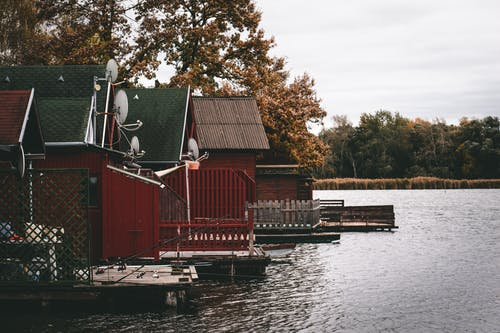 Red and White Wooden House Beside Body of Water