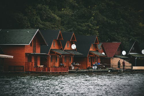 Brown Wooden Houses Near Body of Water