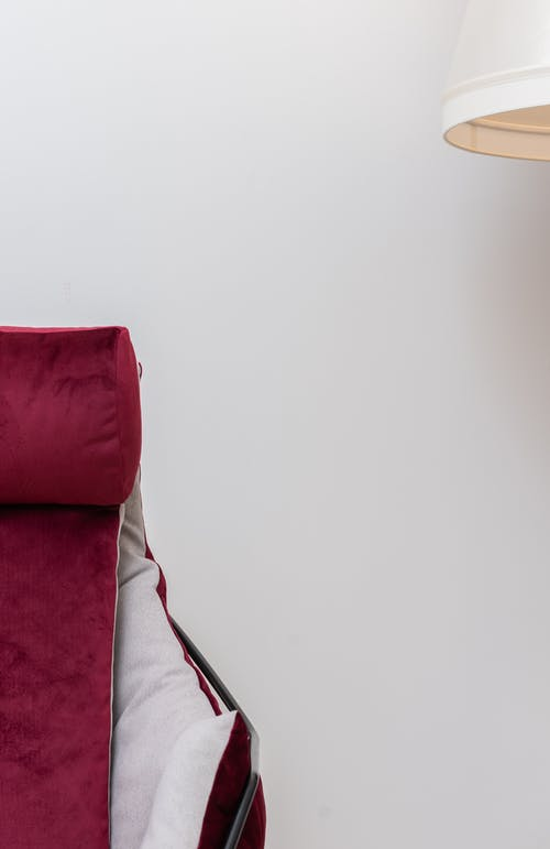 Detail of comfortable soft red armchair with armrest and part of white floor lamp placed on white background in light room