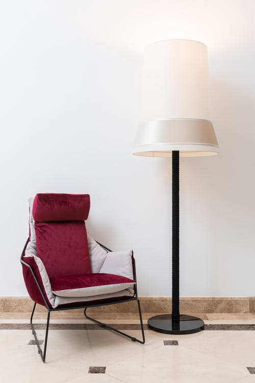 Comfortable armchair and lamp near white wall