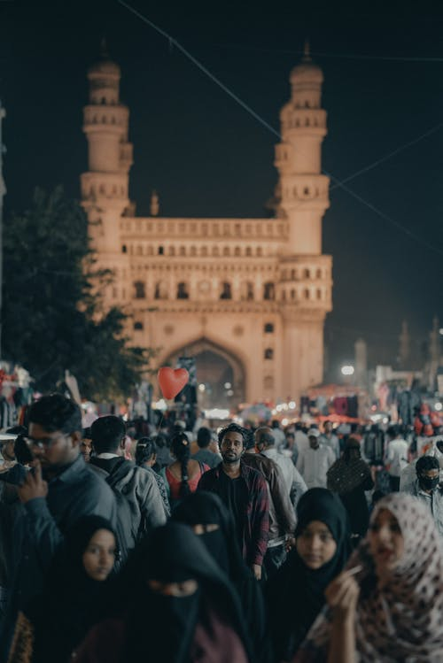 Indian people on city street against old monument
