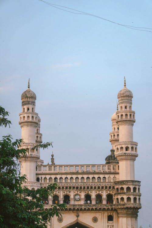 Aged stone mosque with bell towers and decor under cloudy sky in Hyderabad India