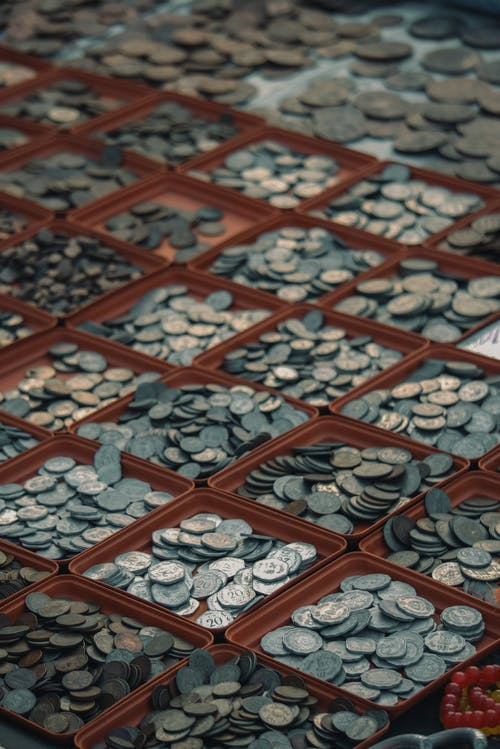 Collection of old coins in boxes on market counter