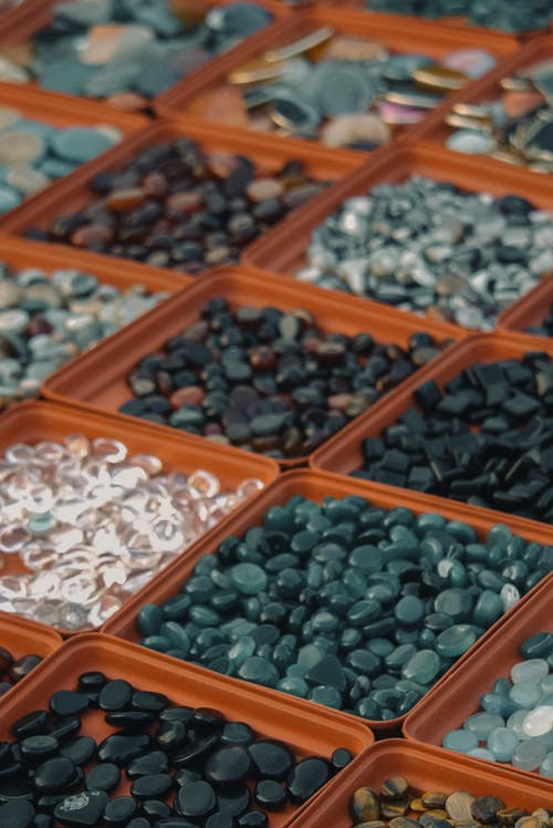 Textured background of collection of small stones in square shaped containers on counter in local bazaar