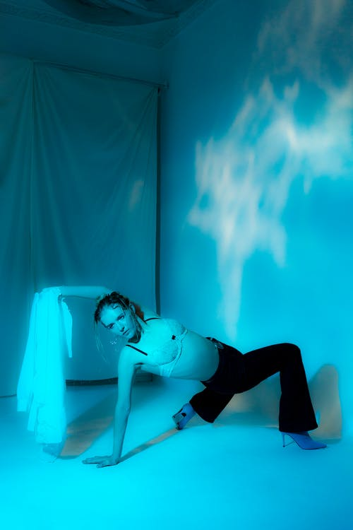 Woman in bra leaning on floor in dark room