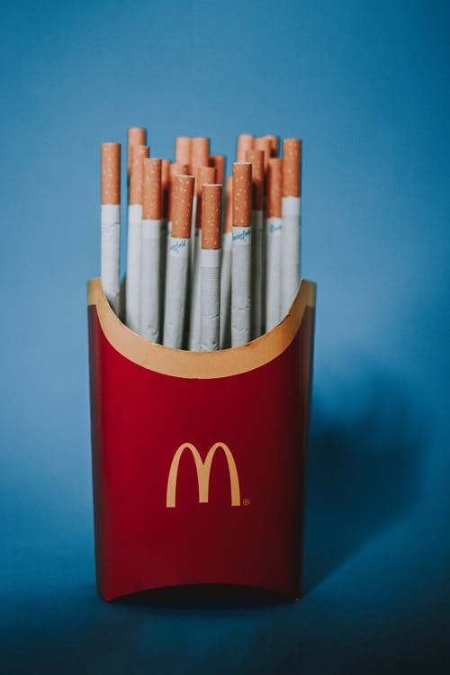Red and yellow paper packet from french fries filled with cigarettes on blue background