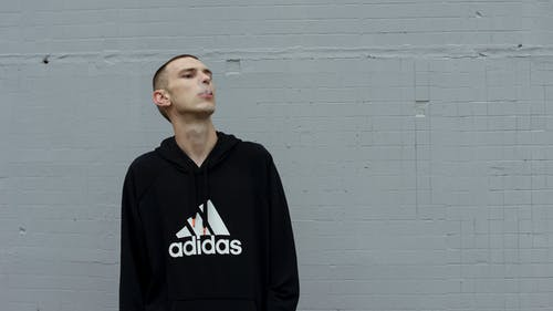 Photo of Smoking Man in Black and White Adidas Hooded Standing In Front of Gray Wall