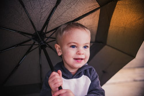 Boy in Gray and White Hoodie Holding Umbrella
