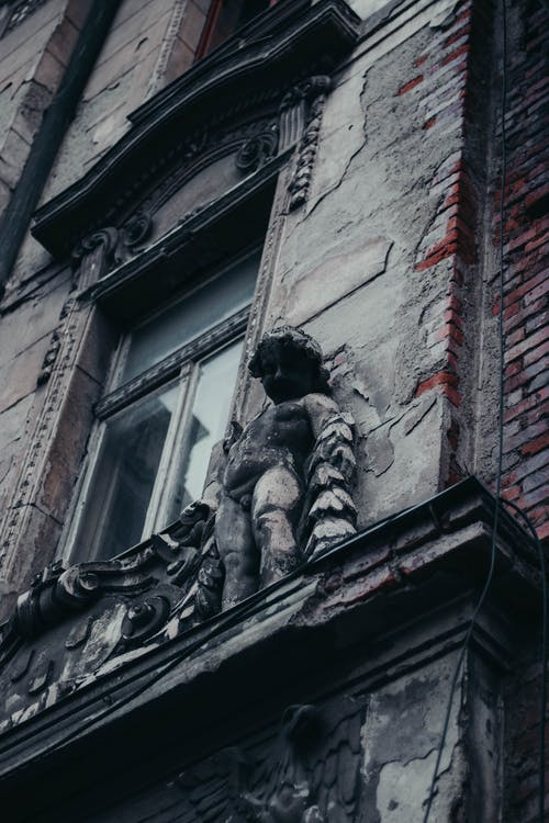 Gray Concrete Statue of Man on Top of Building