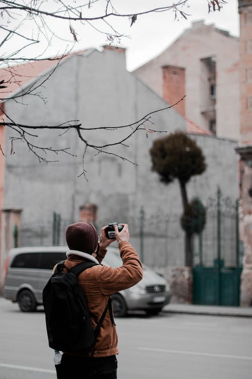 Man in Black and Orange Jacket Taking Photo of Brown Tree