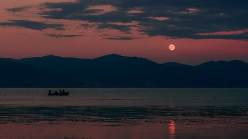 Silhouettes of people floating in boat on calm rippling sea water against mountains at cloudy sunset