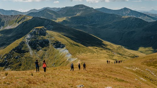 Picturesque landscape of rocky mountainous terrain covered with green grass with group of hiking travelers
