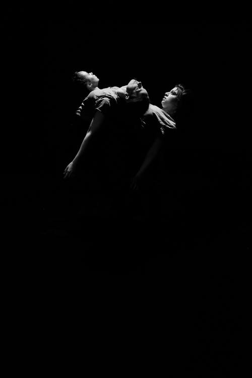Black and white of sensual actors in theatre performing expressive dance together in darkness