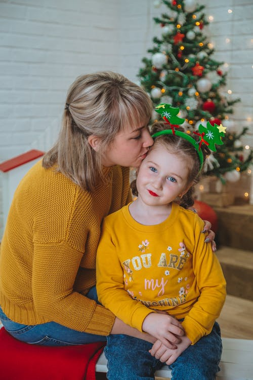 Happy woman kissing daughter in Christmas holidays