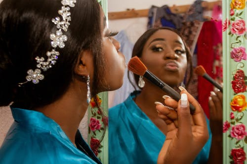 Side view of crop elegant African American female with pouting lips and cosmetic brush reflecting in mirror at home