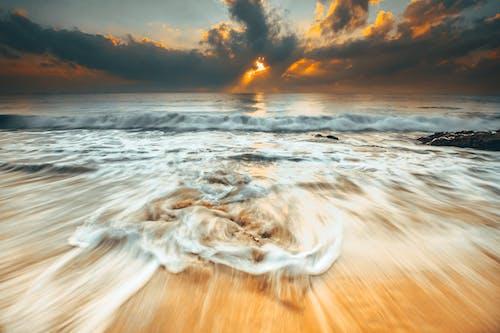 Foamy waves on sandy beach in overcast evening