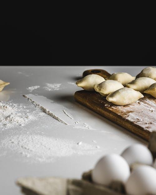 White Flour on White Surface Near Doughs