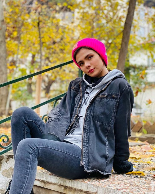 Woman in Tattered Blue Denim Jacket and Pink Beanie Sitting Near Green Handrail