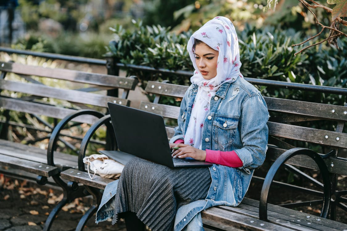 Serious Muslim woman working on laptop in park