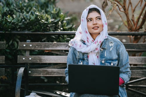 Dreamy ethnic woman browsing laptop while sitting on bench in park