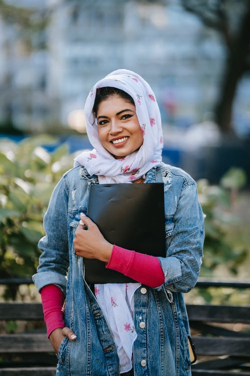 Smiling ethnic lady standing with black folder near city garden