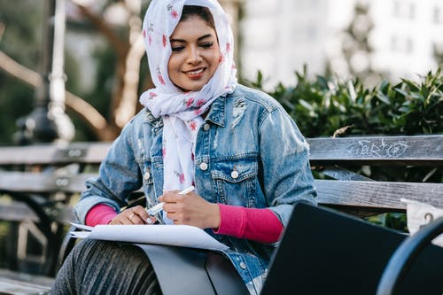Smiling ethnic woman working with papers while sitting in park