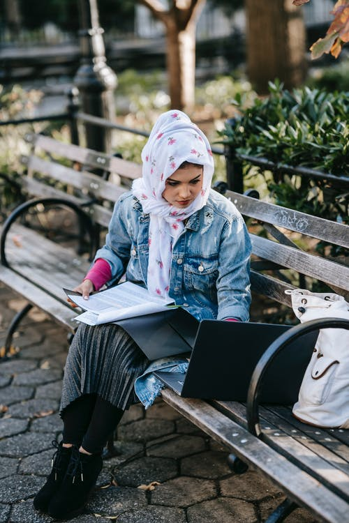 Young ethnic woman typing on laptop in park