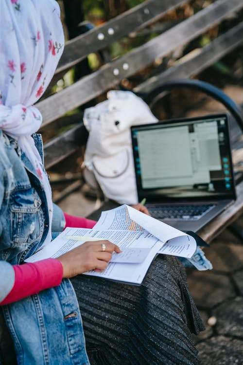 Crop woman in headscarf sitting on bench with paperwork and laptop