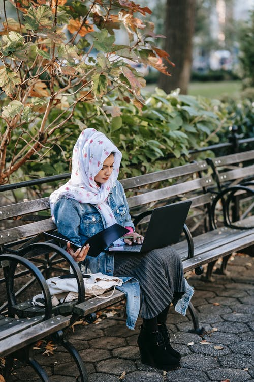 Focused young ethnic woman surfing laptop while sitting with documents in park