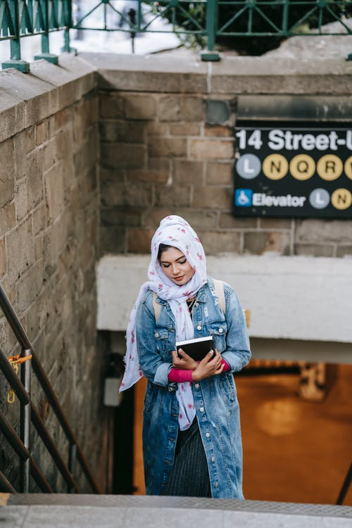 Young Muslim lady walking upstairs from subway in megapolis